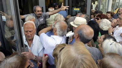 Pensioners line up as they wait to be allowed into a bank to withdraw a maximum of $134 for the week [Daniel Ochoa de Olza/AP]