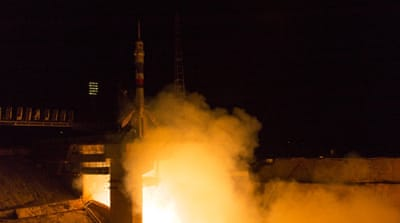 The spacecraft carrying the three astronauts from Japan, Russia and US docked six hours after it launched, NASA said [AP]