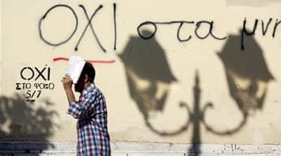 A man shelters from the sun as he walks past graffiti that reads 'No' in Greek in Athens [REUTERS]