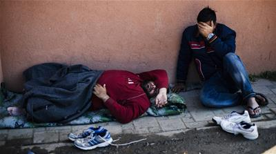 A migrant couple sleeps near a police station in the southern Serbian town of Presevo [AFP]