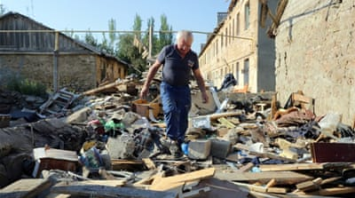 A man walks through the rubble of his destroyed house in Golmovsky after shelling between Ukrainian forces and separatists [AFP]