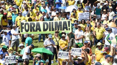 Protesters carry banners saying 'Out Dilma' and demand the international community not to recognise her as president[Getty Images]