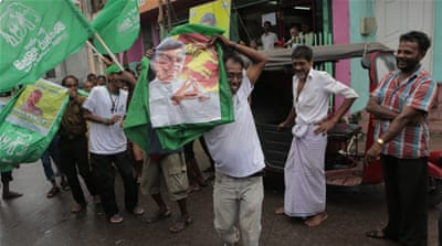 Supporters carry a portrait of PM Wickremasinghe as they celebrate their party''s election performance [AP]