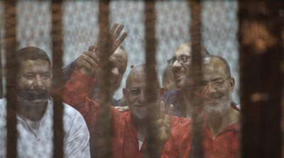 Egyptian defendants Badie, centre, at the Police Academy [AP]