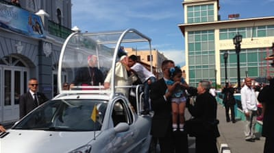 Pope Francis stops to embrace a child while approaching a cathedral in Santiago, Cuba [Lucia Newman / Al Jazeera]