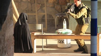 A photo supplied by an activist group shows a soldier pointing a gun at the young woman [Supplied by Youth Against Settlements]