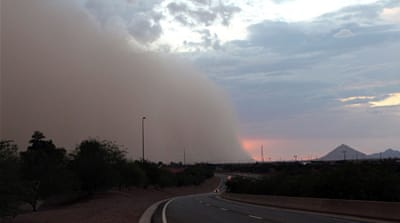 A giant dust storm gathers ahead of a recent downpour, over the countryside in rural Mesa, Arizona [EPA]
