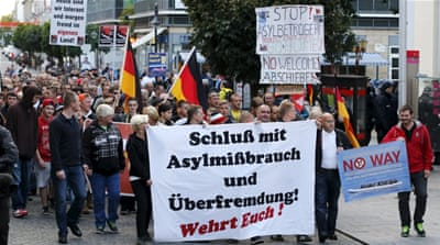 Far-right protesters carry a banner reading 'Stop the asylum abuse and excessive foreign infiltration!' [Reuters]