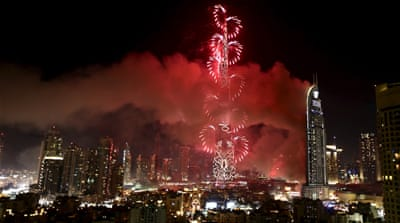 The fire at the Address Hotel continued to burn during a fireworks display at the nearby Burj Khalifa, the world's tallest building [Ahmed Jadallah/Reuters]