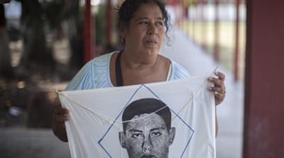 Yolanda Gonzalez holds a kite bearing the image of her son, Jonas, one of the 43 students who went missing in Iguala, Guerrero, southwestern Mexico, in 2014 [Eduardo Miranda/Al Jazeera]