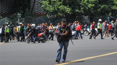 A man is seen holding a gun as people run away in central Jakarta, Indonesia [Reuters]