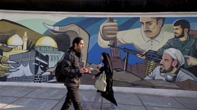 Iranians walk past a revolutionary mural in Tehran, Iran [REUTERS]