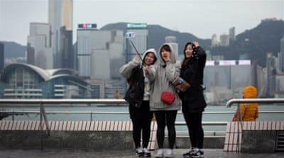 Tourists shiver as temperatures in Hong Kong plunge to their lowest point in nearly 60 years. [AFP]