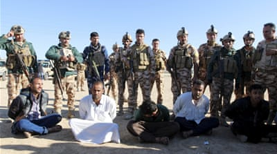 Kurdish peshmerga forces stand near detained men, suspected of being linked to an attack near Kirkuk [REUTERS]