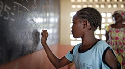 A girl working out sums at the blackboard during a math lesson at a refugee camp in Bangui [Getty]