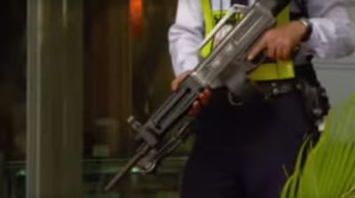 Screen grab of a police officer holding a rifle.