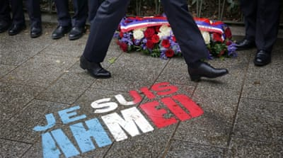 Policemen walk past graffiti on the pavement reading: 'Je suis Ahmed', referring to the police officer Ahmed Merabet shot dead on the day of the Charlie Hebdo attack [AP]