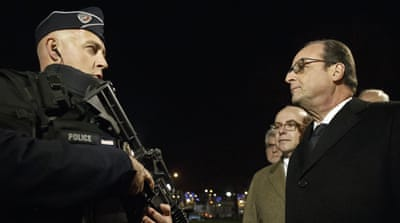 Hollande talks to an armed police officer as he visits the security measures at the Champs Elysees in Paris [AP]
