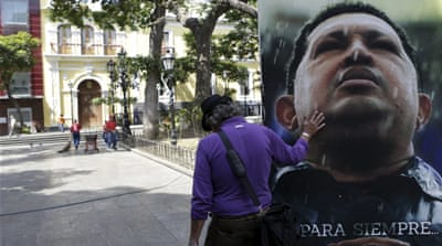 Maduro's supporters gathered in front of portraits of Chavez and revolutionary hero Simon Bolivar [Reuters]