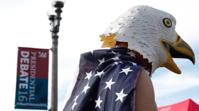 A man wears an eagle mask and a US flag outside the debate between Trump and Clinton in Missouri, US [REUTERS]