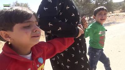 This video grab shows children who survived the air strike on the village of Hass on Wednesday [Revolutionary Forces of Syria, via AP]