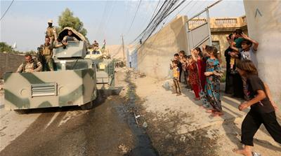 A Kurdish Peshmerga fighter takes a selfie with children after recapturing Fadiliya village [Air Jalal/Reuters]