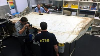 File: An undated handout picture shows Malaysian and Australian investigators examining a piece of aircraft debris [EPA]