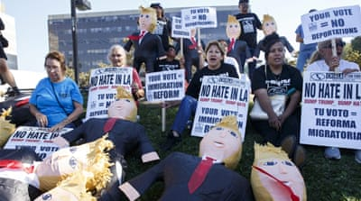 Protesters chant next to Donald Trump pinatas as they encourage Latinos to register to vote in Norwalk, California [EPA]