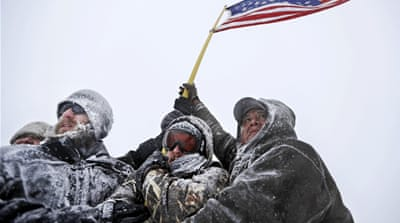 Military veterans huddle together to hold a US flag against strong winds outside the Oceti Sakowin camp in Cannon Ball, North Dakota [David Goldman/AP]
