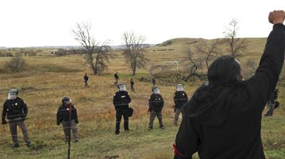 A Dakota Access pipeline protester defies law enforcement officers who are trying to force them from a camp on private land in the path of pipeline construction near Cannon Ball [James MacPherson/AP]