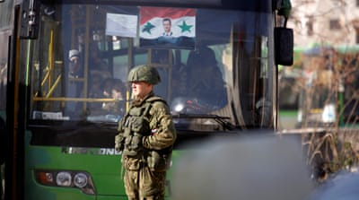 A Russian soldier stands near a bus in government-controlled Hanono district in Aleppo on Sunday [Omar Sanadiki/Reuters]