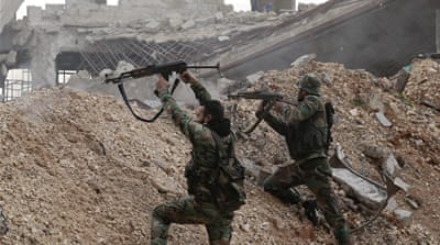 Syrian soldiers fire weapons during a battle with rebels at the Ramouseh frontline in east Aleppo [Hassan Ammar/AP]