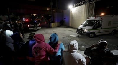 Family members of inmates stand outside Topo Chico Prison as an ambulance leaves the compound [Daniel Becerril/Reuters]
