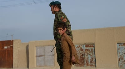 A wounded Afghan boy walks with an Afghan soldier at the site of a suicide attack in Mazar-i-Sharif [Getty]