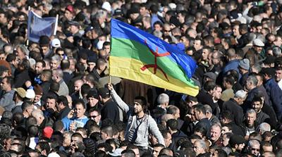 A man waves the Amazigh flag at the funeral of one of the fathers of Algeria's struggle for independence [AFP]