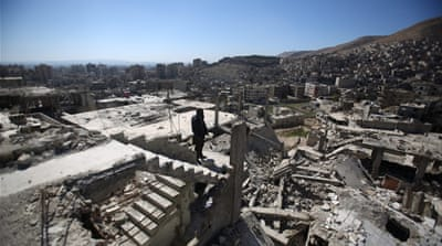 A Syrian man stands on top of a damaged building in Barzeh neighborhood of Damascus, Syria [EPA]