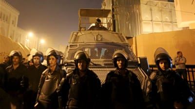 Riot police officers stand guard in front of the Cairo Security Directorate [Reuters]