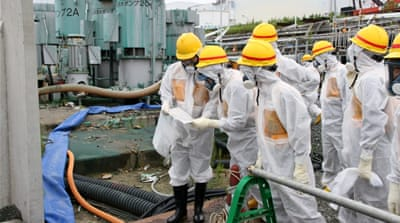 Workers wearing protective suits inspect the damaged Fukushima Dai-ichi nuclear power plant in August 2013 [EPA]