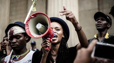 Final-year BA student Busisiwe Seabe addresses a crowd of protesters outside the university's Great Hall [Cornel van Heerden/Al Jazeera]