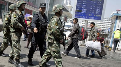 Paramilitary police pass the site of an explosion in China's restive Xinjiang region in 2014 [File: Ng Han Guan/AP]