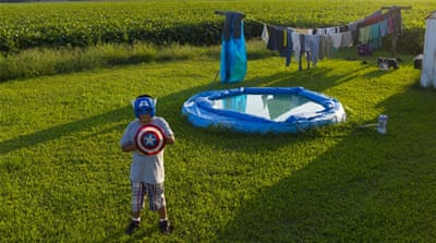 The child of Mexican farm labourers plays with his Captain America toys in the back yard of his home in rural Sampson County, North Carolina [Andrew Lichtenstein/Al Jazeera]