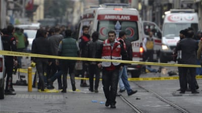 A woman places carnations at the scene of a suicide bombing at Istiklal street [Osman Orsal/Reuters]
