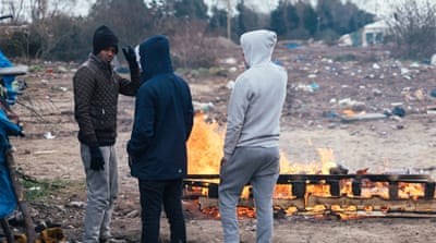 Refugees stand among the remains of the Kurdish and Eritrean areas of Calais' 'the Jungle' after French authorities bulldozed this part of the camp [James Rippingale/Al Jazeera]