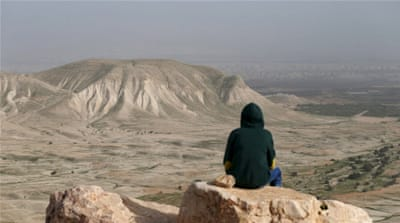 A Palestinian man sits on a rock at Jordan Valley near the West Bank city of Jericho [REUTERS]