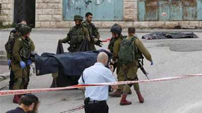 Israeli soldiers stand near the body of Palestinian who was shot while laying wounded on the ground after an alleged attack in Hebron [AP]