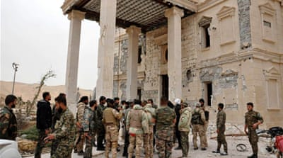 Syrian government soldiers gather outside a damaged palace in Palmyra, Syria, amid a fierce battle for control over the ancient city [SANA/AP]