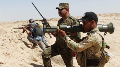 Iraqi soldiers with new US-made weapons take positions at the front line against ISIL in August 2015 [AP]