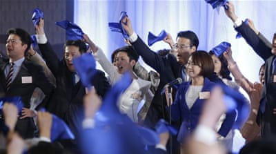 Japan's new opposition Democratic Party leader Katsuya Okada, centre right, punches the air with politicians and supporters during the convention of its inauguration in Tokyo [Shizuo Kambayashi/AP]