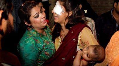 A woman injured in the bomb blast is comforted by a family member at a local hospital in Lahore, Pakistan [AP]
