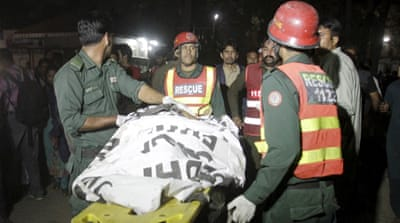 Rescue workers move a body from the site of the blast outside a public park in Lahore, Pakistan [Mohsin Raza/Reuters]